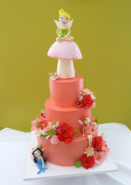 tink    Three tier cake iced in buttercream. Gumpaste mushroom and fairy characters.   Handmade sugar flowers.