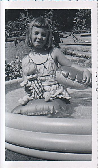 Little girl in wading pool with her doll; 1956.