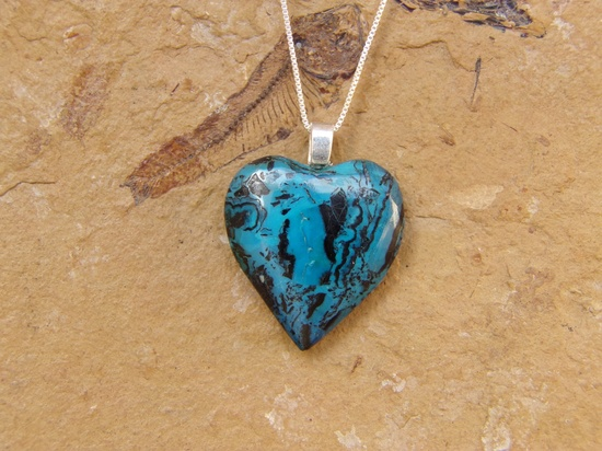 """Beautifully handcrafted heart pendant made from chrysocolla from Mexico."" Love the color of this stone! (And the fossilized ""critter"" in the background!)"