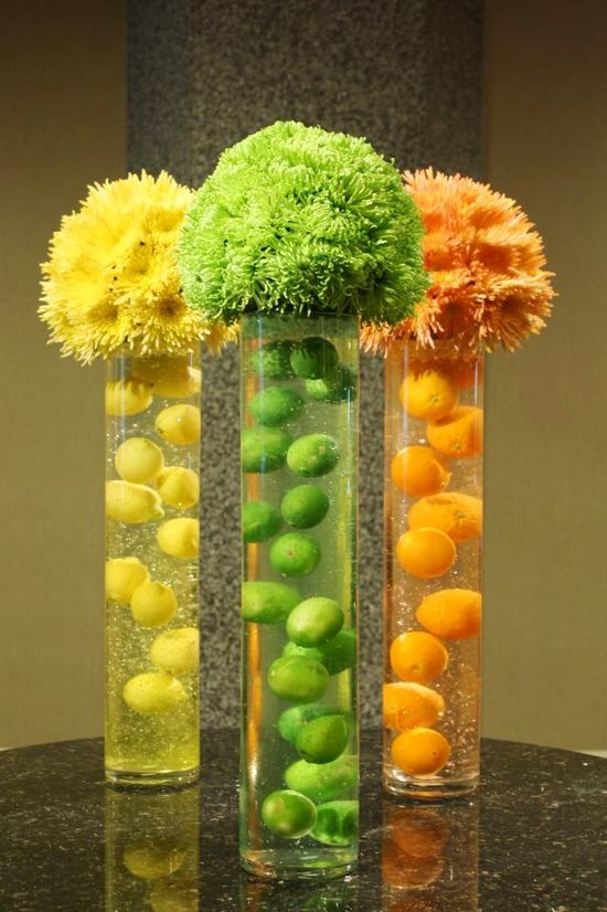 """""""Citrus Surprise"""" Cool icy and refreshing. A gelatin like material suspends fresh citrus fruits in tall glass cylinders. Spheres of spider mums top these citrus coolers."""