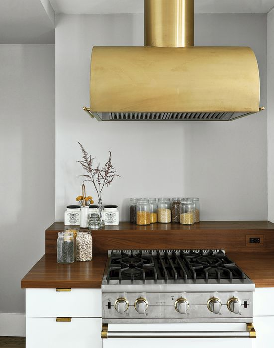 The Viking gas range is shown in Cotton White and finished in polished brass details to match the Workstead-designed hood.