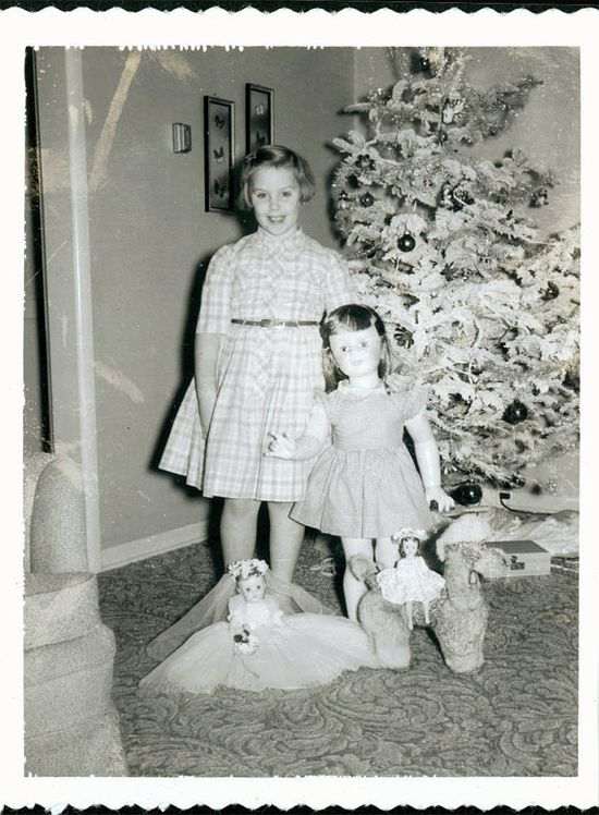 Vintage photo of a young girl in front of Christmas tree with dolls, 1950's.