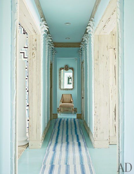 Miles Redd ~ A hallway, painted in a Benjamin Moore blue, is lined with plaster palm trees; rugs from IKEA were stitched together to make the runner in this home in the Bahamas.