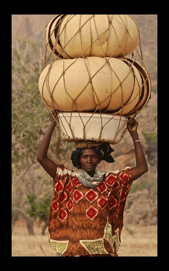 Mali. Dogan woman walking with a  bulky load