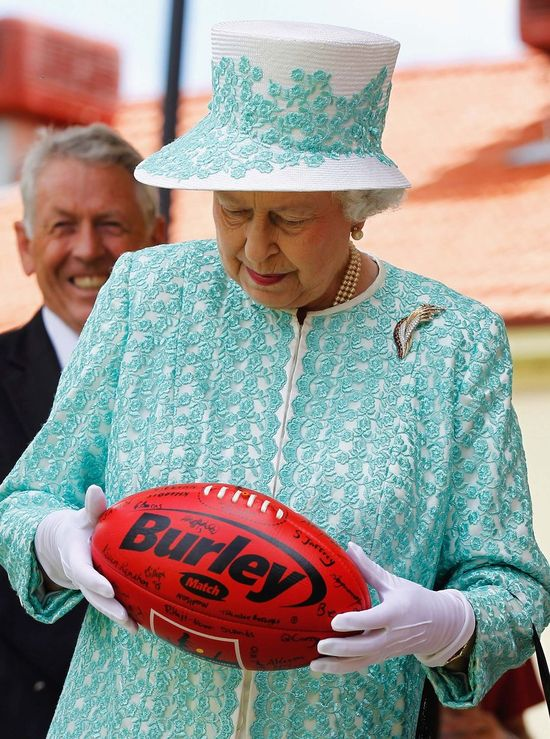 Queen Elizabeth II looks at an Australian rules football during her visit to Clontarf Aboriginal college on October 27, 2011 in Perth