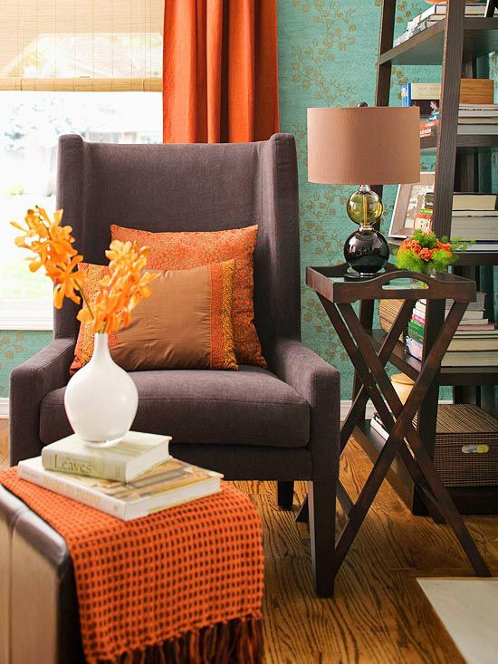 ORANGE: Brighten Your Outlook  Deep color creates a cozy ambiance in this sitting area. A curvy vine pattern on blue-green wallpaper softens the masculine lines of the dark wood shelving and brown wing chair. To keep the room lively, vibrant orange curtain panels frame the window while orange pillows prevent the chair from becoming a dark mass in the room. Orange accents, such as a small runner on the side table dot the room with the peppy hue.