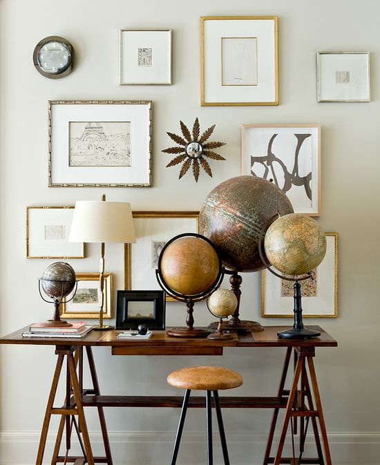 Suzanne Kasler uses collections to create impact, like this collection of antique globes which pairs beautifully with warm wooden furniture pieces and a gallery wall of art with gilded frames