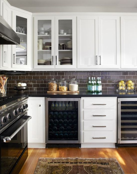 Love the white cabinets with the stainless steel appliances. The Gas Range stove is amazing with the range hood. We would change the tile to either a white subway tile with black glass tile or a stone tile.