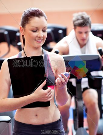 stock photo of joyful coach holding a chronometer with man in the background doing physical exercises in a fitness centre