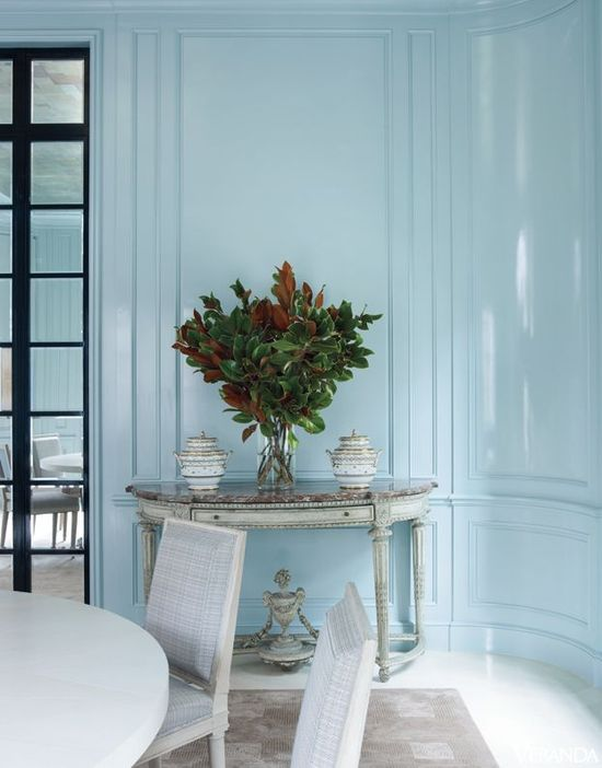Sky blue gloss paneled walls in an oval dining room by David Kleinberg.