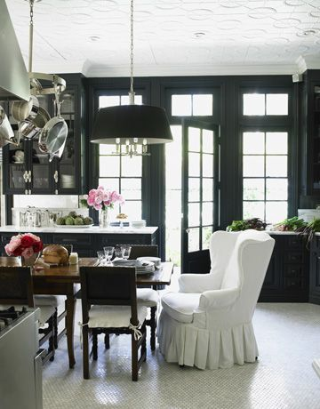 the black trimmed wall of windows & doors, the white tufted dining chair, the natural light, the white patterned ceiling...Windsor Smith did her own kitchen RIGHT.
