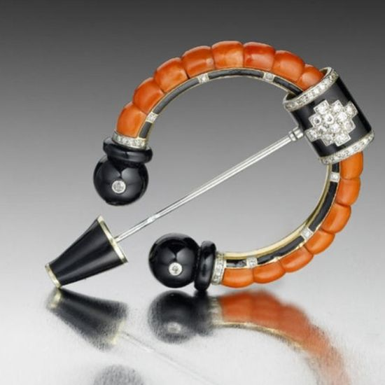 A fine art deco onyx, coral, enamel and diamond penannular brooch, by Cartier, circa 1925