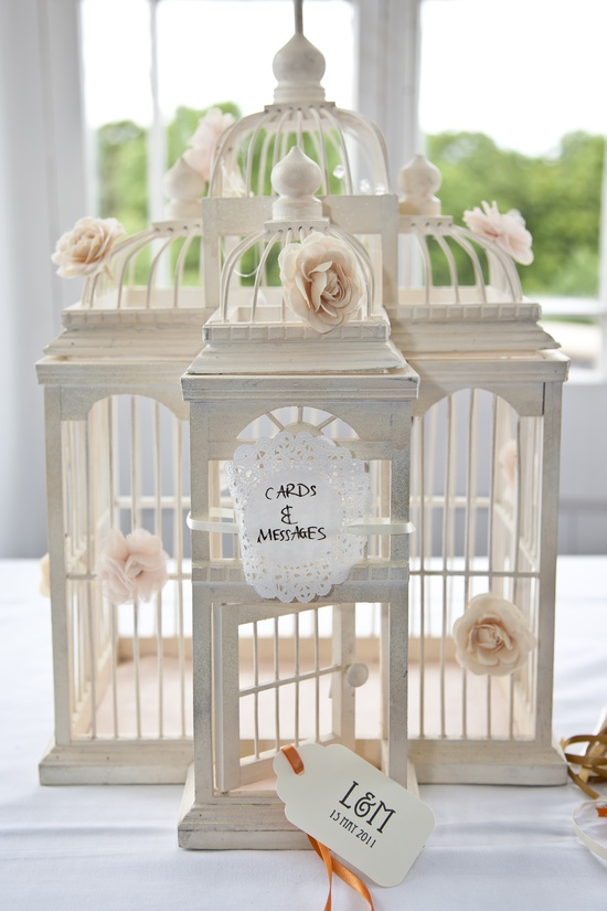 Decorated birdcage to tie in with my vintage theme (peach and cream), using hair flower clips (H), a doily, tags & ribbons (ebay)