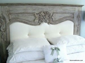 Repurpose a vintage fireplace mantle as a headboard for a bed.