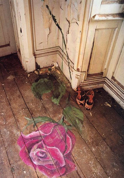 worn wooden floors, chippy walls and a beautiful hand painted rose on the floor...beautiful...in an abandoned house..