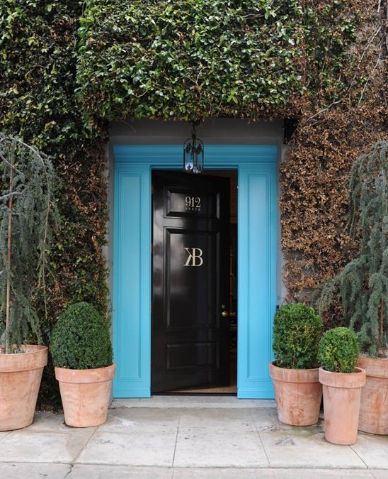 Building exterior with bright blue door and lots of ivy
