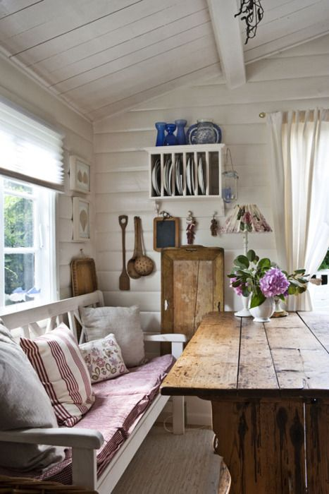 loving all the white, open shelving, wall hooks, the pillows & bench seat plus scrubbed wood table...sweet!