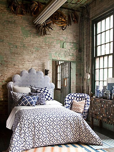 Love this room. Brick wall + paned windows + comfy bed with cool patterns in somewhat muted tones. Soft cloud-like headboard. Nice! (duvet cover by John Robshaw - Saks.com) #interior #decor #bedroom #brick