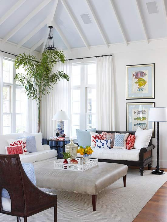Bright red and blue patterned throw pillows look lovely in this all white room. More living room design ideas: www.bhg.com/...