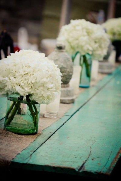 Flower table centrepieces. Hydrangeas in vintage jars. Love!