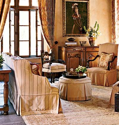 An elegant room with drapes and striped furniture.