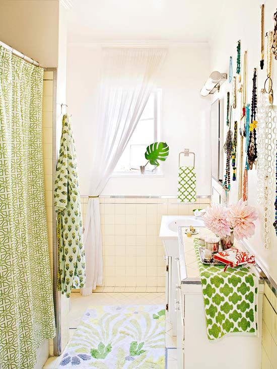 Vintage buildings have plenty of charm, but some original elements can pose a decorating challenge. Rather than cringe at something you don't like, embrace it and find a work-around. If the bathroom tile is a shade you can't stand, pick a color you do like to serve as the room's main hue. The tone of green used in this bathroom has just a twinge of yellow, which helps the accents to stand out and the yellow tile to recede. Try a blue-green with powder blue tile or sherbet orange with salmon-colo