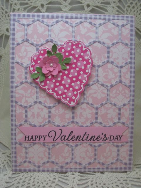 handmade Valentine card ... like the hexagon cover plate die cut from patterned paper and mounted on patterned paper of another color but about the same tonal quality ... die cut heart stands out in darker p;rint paper ...