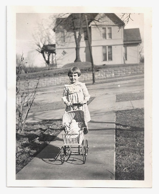 Vintage photo of little girl with doll circa 1920.
