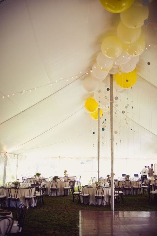 Balloons of different sizes in wedding colors, filled with helium, let go to rest at top of tent