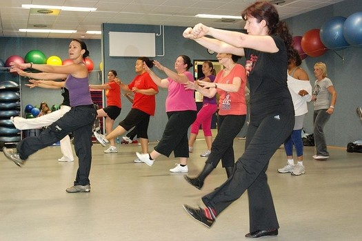 An instructor coaches a Zumba class in a fitness center. This is my article on a Groupon.