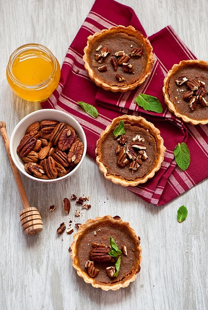 The marriage of two timeless autumn pies (in portable hand-size): Pumpkin-Pecan Tarts. #pie #tarts #tartlets #dessert #autumn #fall #dessert #pumpkin #pecan