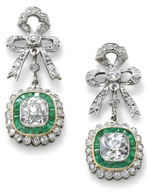 A pair of diamond and emerald ear pendantsl. The brilliant-cut diamond bow surmount suspending a centrally-set cushion-cut diamond with a millegrain-set calibre-cut emerald and old brilliant-cut diamond cluster, diamonds approximately 2.00 carats total, length 2.5 cm. Via Phillips.