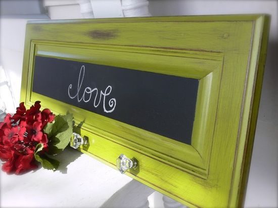 LOVE LOVE LOVE!!  old cabinet door painted, center painted with chalkboard paint, knobs attached and used for hanging jackets, etc.