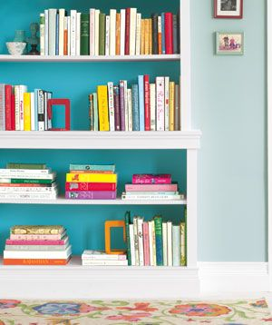 Borrow a trick from interior designers: Inside a bookcase, use paint that's a couple shades deeper than the room color. I'd have to paint our bookshelves white first maybe. Or maybe paint the whole bookshelf the darker shade?