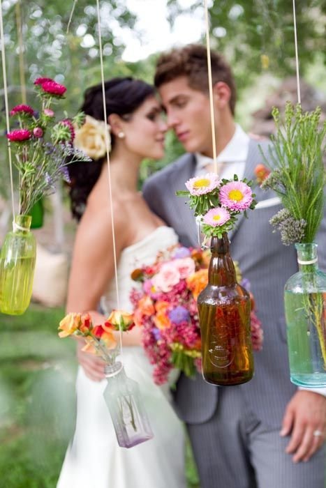 Hanging bottles. Love the different shapes & colours of the bottles with all different flowers in them.