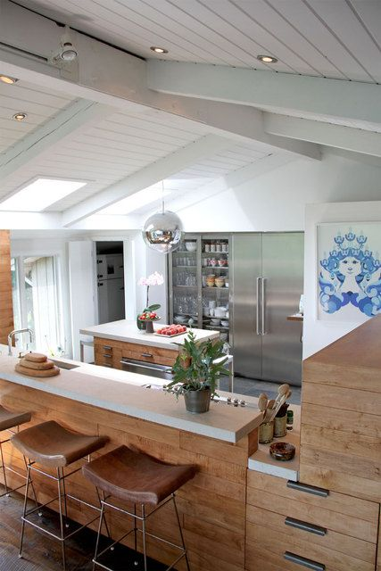 wood cabinets warm up a white and stainless steel kitchen