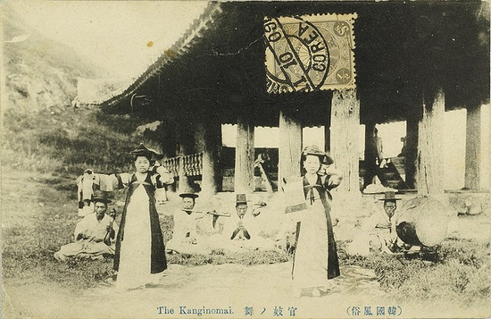 "The Korean kisaeng were professional girls trained in music, dance, and poetry. ""Official kisaeng"" (?? ??), as depicted in this vintage postcard, were employed by the government and performed at ceremonial banquets. In the background, an ensemble playing traditional Korean instruments. The building in the background is Pubyok Pavilion by kernbeisser"