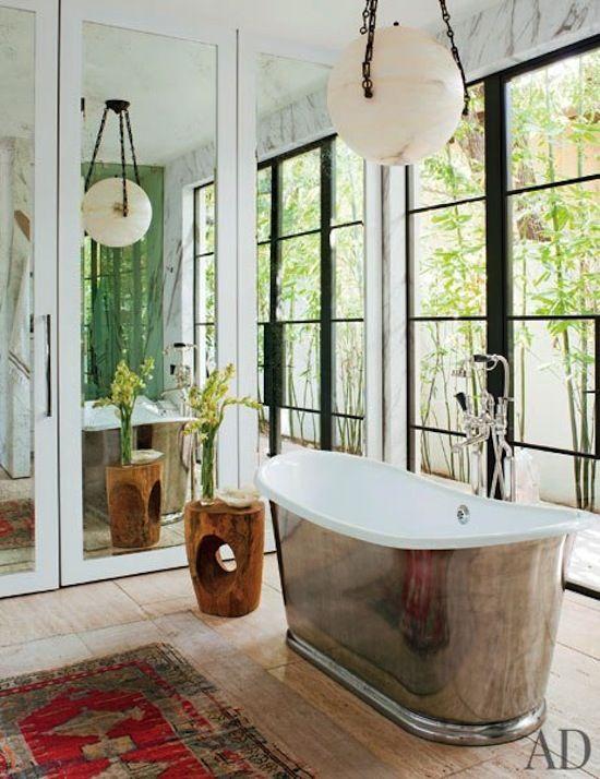 large silver soaking tub, alabaster round mod light fixture, black iron window panes