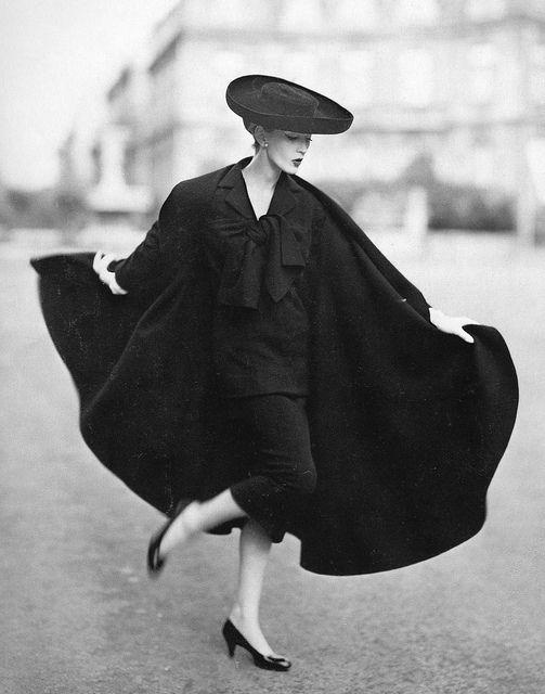 Dovima in cape ensemble by Lanvin-Castillo. Photo by Avedon; Place Francois-Premier, Paris, August 1955.