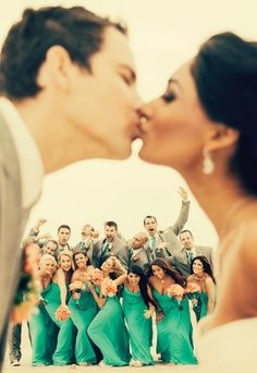 Cute shot of bride and groom kissing with wedding party behind them.  Wedding Photo.