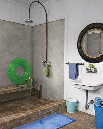 This summer cottage downstairs bathroom features a double-wide shower with the same stone floors used throughout the property's barn. Its open layout is perfect for rinsing off after a swim.