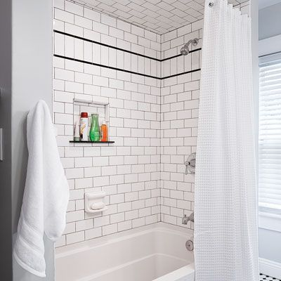 Smoke-colored grout and a row of subways turned on end and bordered with black trim add character to this tub alcove.