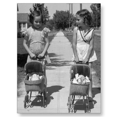 Friends taking their dolls for a walk. Circa 1940.
