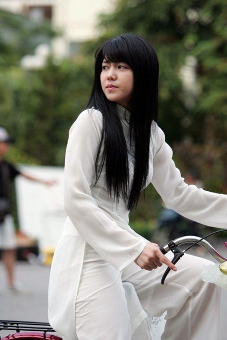 Vietnamese girl wearing an ao dai on a bicycle.