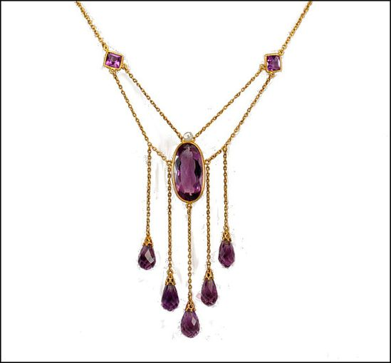 Edwardian / Victorian14K gold amethyst and pearl antique necklace! A large oval bezel set genuine amethyst stone is band wrapped in gold with five dangling faceted amethyst pendants swinging below. Each pendant is topped with a gold filigree bale and connected to a long chain. The large center pendant has a fresh water pearl at the top and connected via swag chains to two diamond shaped amethyst stations /750.00
