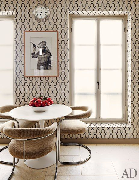 In a Monte Carlo dining area, a Saarinen table by Knoll is paired with vintage Milo Baughman chairs, a Moroccan-inspired wallpaper by Phillip Jeffries, and a photograph by Marie-Laure de Decker.