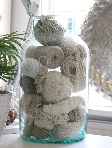 linen colored balls of string in a giant glass jar