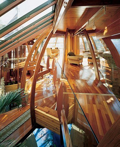 mixture of wood and glass curved walls and ceiling water and foliage elements widened middle section egg shaped framework