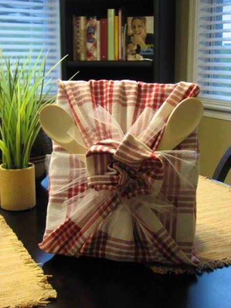 A fun wedding/christmas gift! A cookbook wrapped in dish towels and wooden spoons