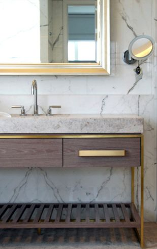 Contemporary with classic elements .  gray wood vanity, gold brass hardware, white carrera marble bathroom